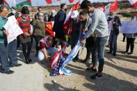 Demonstrators burn Israeli and American flags as they protest against talks on disputed maritime borders with Israel, in Naqoura, near the Lebanese-Israeli border