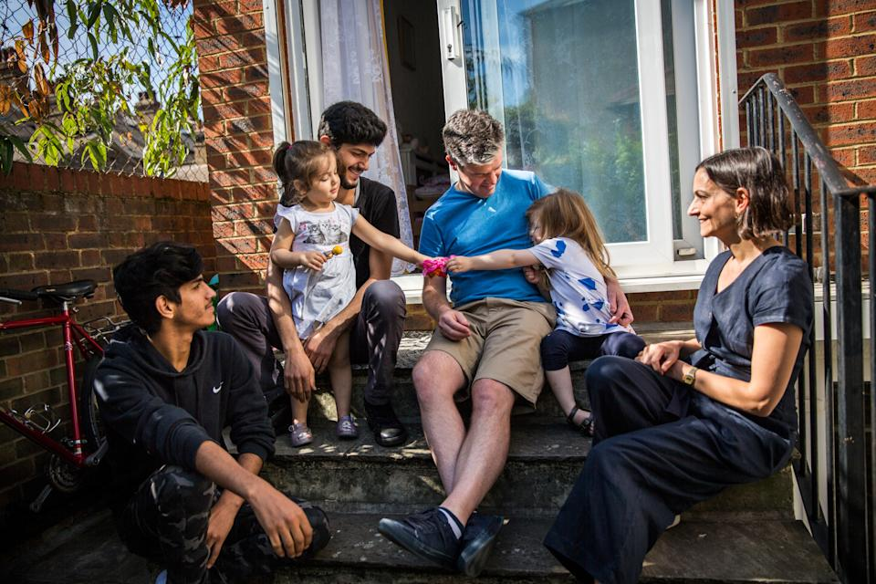 <p>James Lynch (in blue), his daughter, and Claire Tillotson (right), from the Peckham Sponsors Refugees local residents group, socialise with Mohammed Al-Shaabin (top-left), his daughter Celen, and his brother Islam – all of whom fled Syria in 2011 – outside their home in south London</p>Andrew McConnel