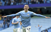 Manchester City's Phil Foden celebrates scoring his side's third goal during the English Premier League soccer match between Manchester City and Everton at the Etihad stadium in Manchester, Sunday, May 23, 2021.(Peter Powel/Pool via AP)