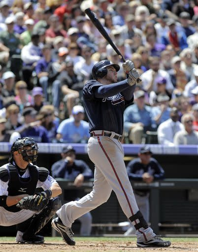 Atlanta Braves' Freddie Freeman watches the flight of a three-run home run ball hit off Colorado Rockies starting pitcher Juan Nicasio during the third inning of a baseball game Sunday, May 6, 2012, in Denver. (AP Photo/Jack Dempsey)