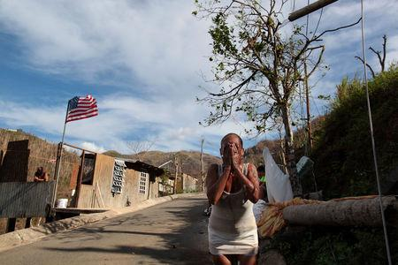 Ruth Santiago refreshes herself with water from a pipe after Hurricane Maria destroyed the town's bridge in San Lorenzo, Morovis, Puerto Rico, October 4, 2017. REUTERS/Alvin Baez
