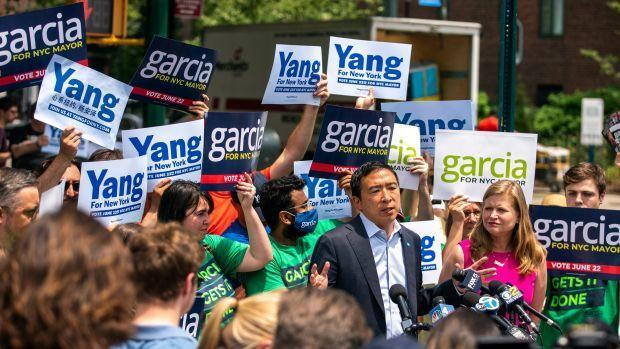 A photograph of Andrew Yang and Kathryn Garcia standing amongst supporters