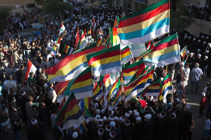 Members of the Druze community of the Israeli-annexed Golan Heights wave their community's flag during a demonstration in the Druze village of Majdal Shams on June 15, 2015 in support of Syrian President Bashar al-Assad's army