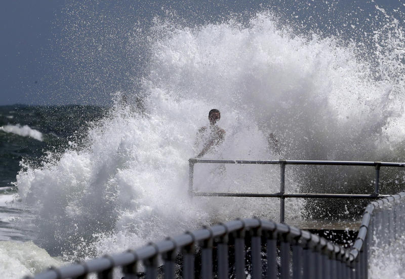 A resident clings to the railing as a wave generated by Hurricane Dorian crashes into the jetty at Lighthouse Point Park in Ponce Inlet, Fla., Monday, Sept. 2, 2019. (Joe Burbank/Orlando Sentinel via AP)