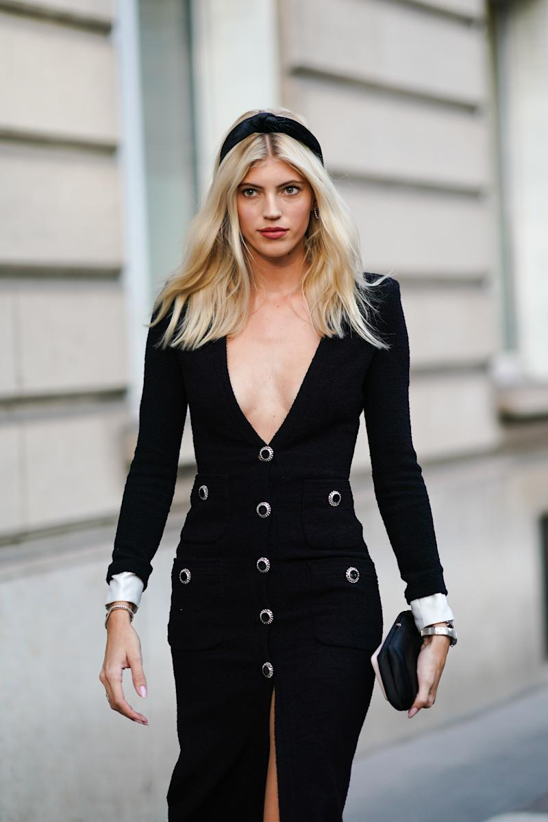 PARIS, FRANCE - SEPTEMBER 27: A guest wears a black headband, a black low neck dress with buttons, a clutch, outside Alessandra Rich, during Paris Fashion Week - Womenswear Spring Summer 2020, on September 27, 2019 in Paris, France. (Photo by Edward Berthelot/Getty Images)
