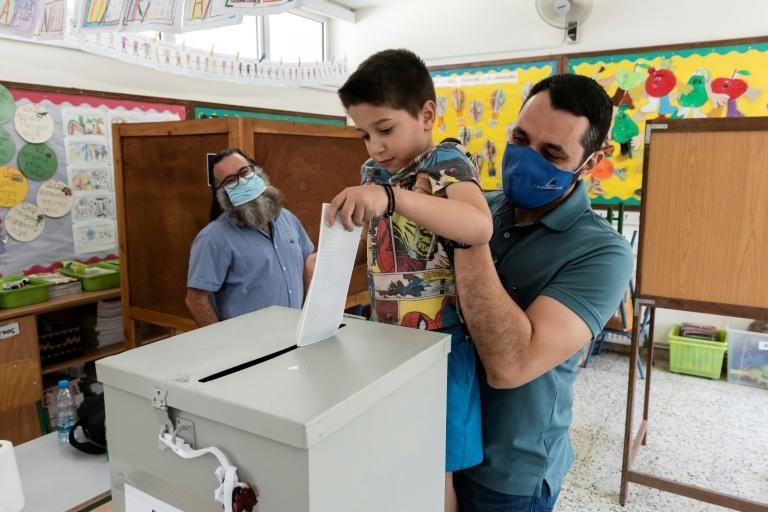 A Cypriot man holds his son up to cast his ballot at a polling station in Nicosia on May 30, 2021