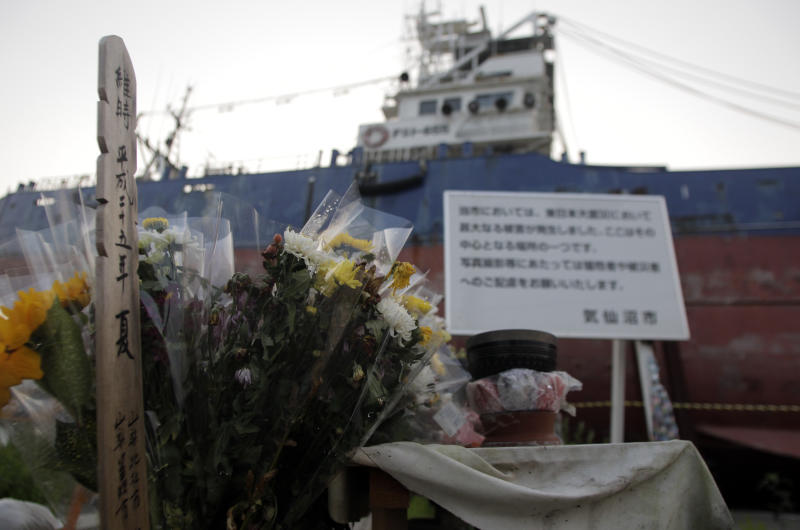 In this photo taken on Sunday Aug. 11, 2013, flowers and gifts are left by a stranded fishing boat standing in a residential district of Kesennuma, Miyagi prefecture, northern Japan. The boat, named Kyotokumaru has become a landmark, but city officials announced last week that it will be torn down. (AP Photo/Azusa Uchikura)