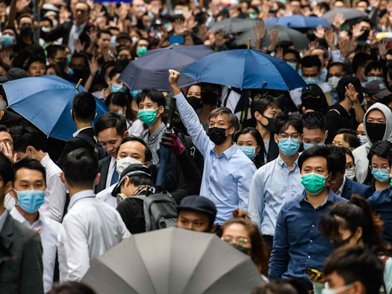 Office workers and pro-democracy protesters gather during a demonstration in Central in Hong Kong on Tuesday: AFP/Getty