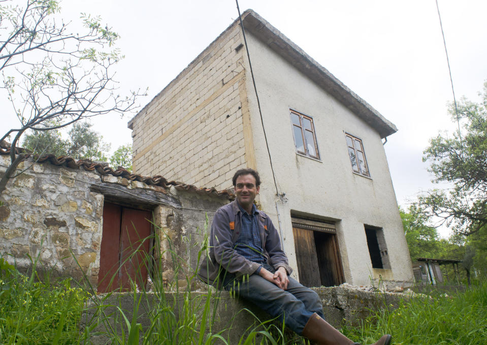 Cain Burdeau sits in front of former barns in Castelbuono, Sicily, on April 13, 2021, that he plans to convert into a family home. (AP Photo/Audrey Rodeman)