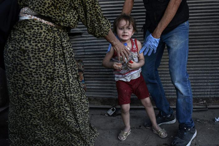 <p>An Iraqi paramedic calms a child, who suffered a shock following a suicide attack as they were escaping the Old City of Mosul, upon their arrival to the area of a field hospital on June 23, 2017. (Photo: Mohamed el-Shahed/AFP/Getty Images) </p>