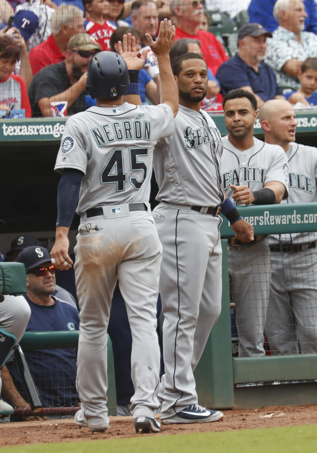 Seattle Mariners' Kristopher Negron (45) is congratulated by Robinson Cano, right, after scoring a run against the Texas Rangers during the third inning of a baseball game, Sunday, Sept. 23, 2018, in Arlington, Texas. (AP Photo/Jim Cowsert)