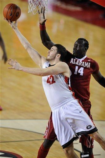 Georgia forward Nemanja Djurisic (42) scores a lay up while defenede by Alabama center Moussa Gueye (14) during the first half of an NCAA college basketball game in Athens, Ga., Tuesday, Feb. 12, 2013. (AP Photo/The Athens Banner-Herald, AJ Reynolds)