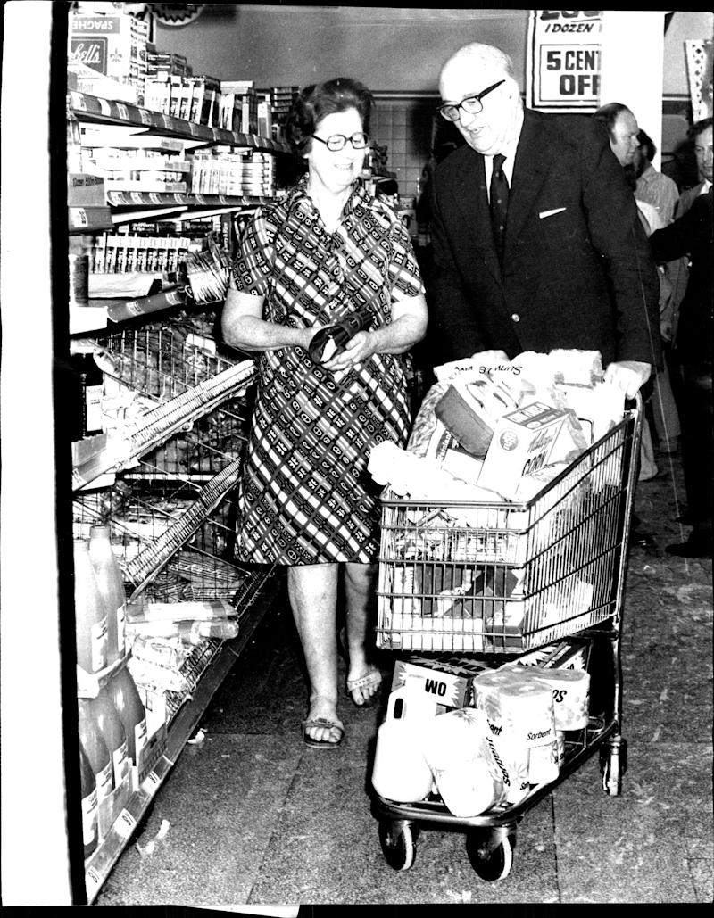 Mrs. M. Quill of Endfield has her laoded trolley pushed through the supermarket by Mr. Norman Coles.The managing director of Coles Supermarkets Mr. Norman Coles today flew from Melbourne to visit the Coles New World Supermarket at Burwood. December 06, 1974. (Photo by Alan Gilbert Purcell/Fairfax Media via Getty Images).