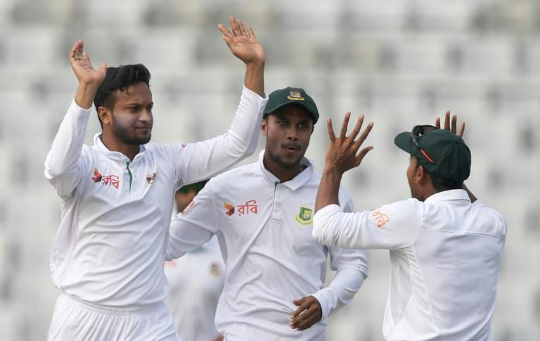 Bangladesh spinner Shakib Al Hasan (L) celebrates taking the wicket of England's Joe Root with teammates on the third day of the second Test at the Sher-e-Bangla National Cricket Stadium in Dhaka on October 30, 2016