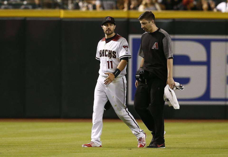 Arizona Diamondbacks center fielder A.J. Pollock (11) leaves the field due to injury as he talks with head athletic trainer Ryan DiPanfilo during the ninth inning of a baseball game against the Milwaukee Brewers, Monday, May 14, 2018, in Phoenix. The Brewers defeated the Diamondbacks 7-2. (AP Photo/Ross D. Franklin)