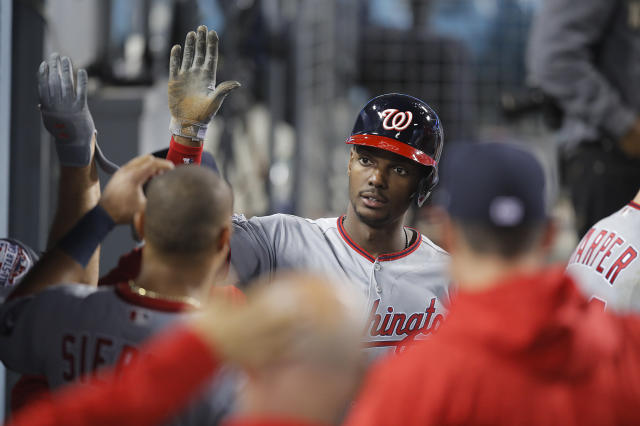 Washington Nationals' Michael Taylor, center, is greeted by teammates after he scored on a bunt by Trea Turner during the fifth inning of a baseball game against the Los Angeles Dodgers, Friday, April 20, 2018, in Los Angeles. (AP Photo/Jae C. Hong)