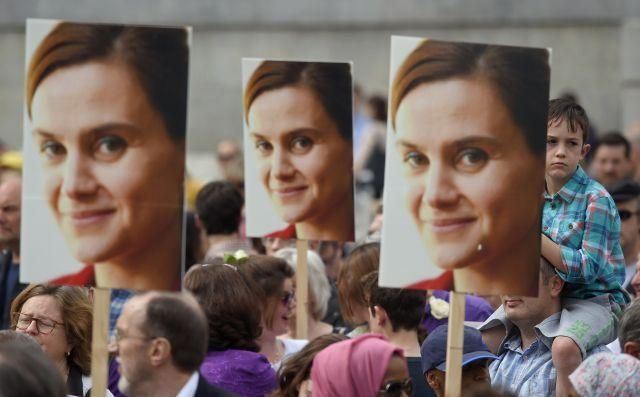 People hold banners of Jo Cox during a special service .