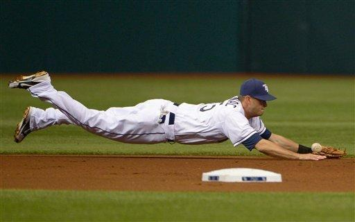 Tampa Bay Rays shortstop Reid Brignac knocks down a single hit up the middle by New York Yankees' Derek Jeter during the first inning of a baseball game in St. Petersburg, Fla., Saturday, April 7, 2012.(AP Photo/Phelan M. Ebenhack)