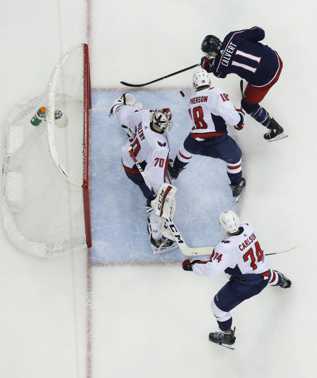 Washington Capitals' Braden Holtby, left, makes a save against Columbus Blue Jackets' Matt Calvert during the second period of Game 6 of an NHL first-round hockey playoff series Monday, April 23, 2018, in Columbus, Ohio. (AP Photo/Jay LaPrete)