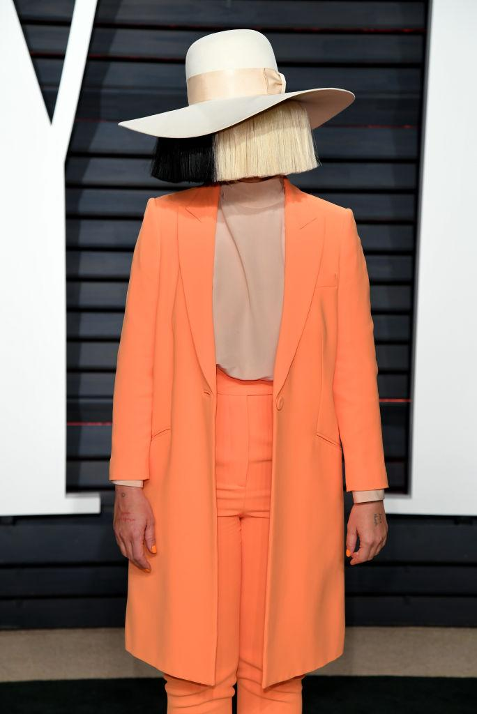 Sia wears an orange suit and a black and blonde wig covering her face at the Vanity Fair Oscar Party in Beverly Hills, Los Angeles, USA on Sunday February 26, 2017.