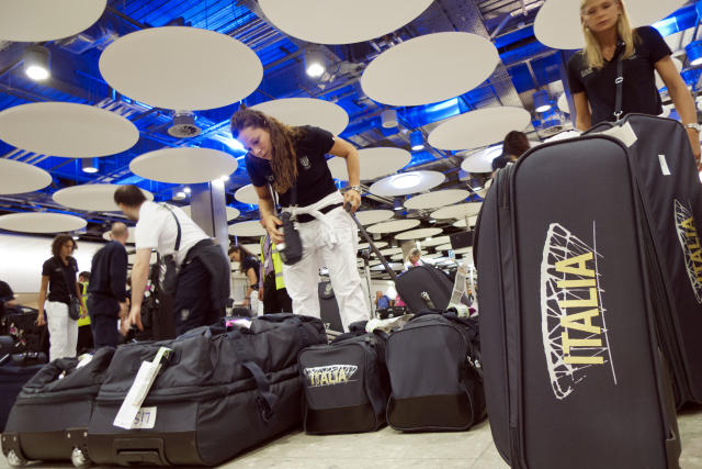 Italian women's volleyball team athletes pick up their luggage as they arrive at London's Heathrow airport to take part at the 2012 Summer Olympics, Tuesday, July 24, 2012. (AP Photo/Andrew Medichini)