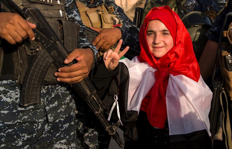 A girl in Mosul flashes the victory sign as she stands with Iraq's federal police forces celebrating the recapture of the city from IS troops on July 9, 2017 (AFP Photo/FADEL SENNA)