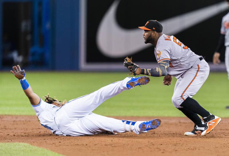 TORONTO, ONTARIO - SEPTEMBER 23: Hanser Alberto #57 of the Baltimore Orioles tags out Vladimir Guerrero Jr. #27 of the Toronto Blue Jays trying to stretch a double in the third inning during their MLB game at the Rogers Centre on September 23, 2019 in Toronto, Canada. (Photo by Mark Blinch/Getty Images)