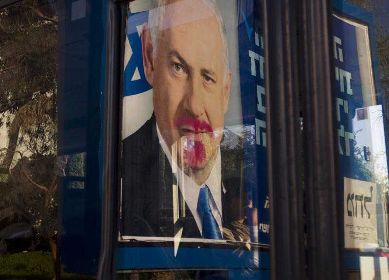 A vandalized election campaign billboard of Israeli Prime Minister and Likud Party leader Benjamin Netanyahu is reflected on a bus window in Tel Aviv, Israel, Monday, Jan. 21, 2013.  The general elections will be held on Tuesday, Jan. 22, 2013. (AP Photo/Ariel Schalit)