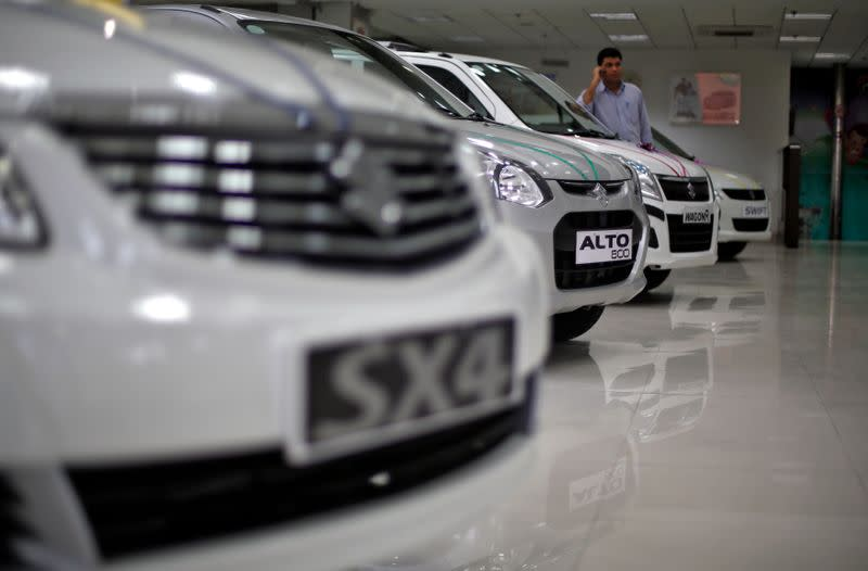 A sales executive speaks on his mobile phone as he stands in between Maruti Suzuki cars inside a showroom in New Delhi