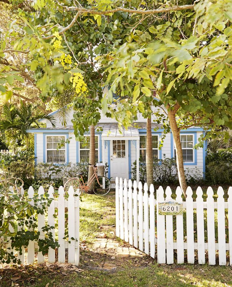 <p>What more could you want from this setting? Pretty blue trim on an adorable cottage? Check. Lush vegetation? Got it. Cool cruiser ready for trip to a nearby farmer's market? Yep. Wide open picketed gate? But of course. <br></p>