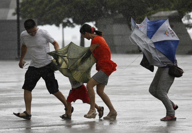 <p> A family battle against the strong wind near the waterfront in Hong Kong Wednesday, Aug. 14, 2013. Typhoon Utor lashed Hong Kong with wind and rain, closing down the bustling Asian financial center Wednesday before sweeping toward mainland China. (AP Photo/Vincent Yu)</p>