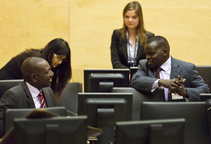 Kenya's Deputy President William Ruto, left, speaks with broadcaster Joshua Sang, right, in the courtroom before their trial at the International Criminal Court (ICC) in The Hague, Netherlands, Tuesday, Sept. 10, 2013. The trial of Kenya's deputy president has opened at the ICC on charges of orchestrating deadly violence in the aftermath of his country's disputed 2007 election. Ruto and broadcaster Joshua Sang are both accused of murder, deportation and persecution. They insist they are innocent. (AP Photo//Michael Kooren, Pool)