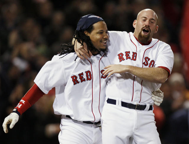 FILE - In this April 30, 2008, file photo, Boston Red Sox's Manny Ramirez, left is hugged by teammate Kevin Youkilis after Ramirez scored the game-winning run on Jason Varitek's RBI single during the ninth inning of their 2-1 win over the Toronto Blue Jays in a baseball game at Fenway Park in Boston. Ramirez and Youkilis have been hired by Chicago Cubs' Theo Epstein, their old boss on the Boston Red Sox. After serving as a player-coach for Triple-A Iowa during the second half of last season, Ramirez was announced Tuesday, Feb. 24, 2015, as the Cubs' hitting consultant. Youkilis was given a part-time job as a scouting and player development consultant. (AP Photo/Winslow Townson, File)