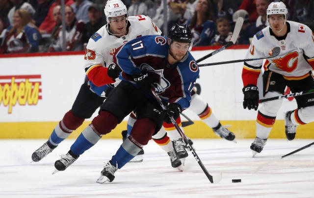 Colorado Avalanche center Tyson Jost, front, picks up the puck as Calgary Flames center Sean Monahan, back left, and center Mikael Backlund pursue in the first period of an NHL hockey game Monday, Dec. 9, 2019, in Denver. (AP Photo/David Zalubowski)