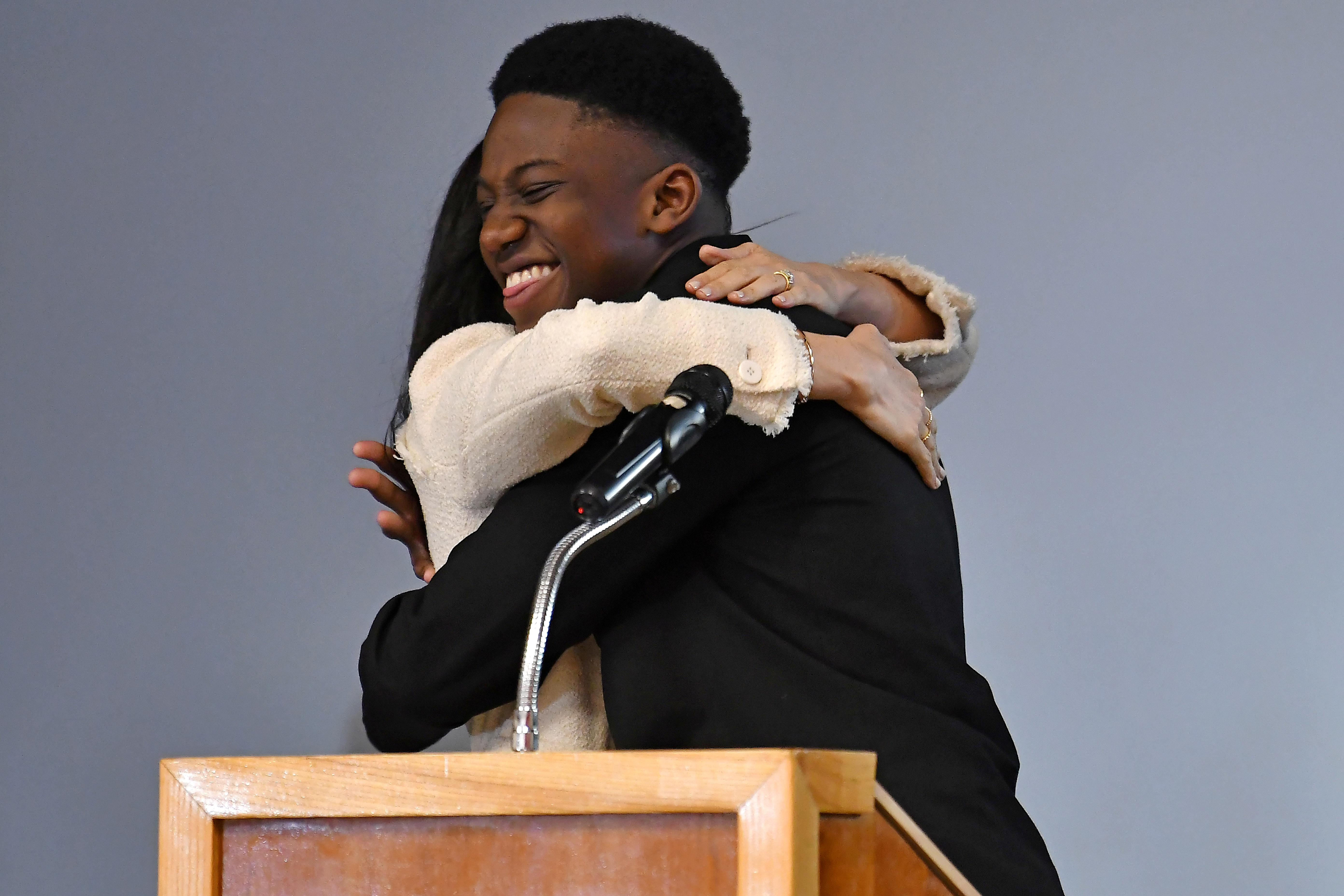 Britain's Meghan, Duchess of Sussex embraces student Aker Okoye during a school assembly as part of a visit to Robert Clack School in Essex, Britain March 6, 2020, in support of International Women's Day. Picture taken March 6, 2020. Ben Stansall/Pool via REUTERS