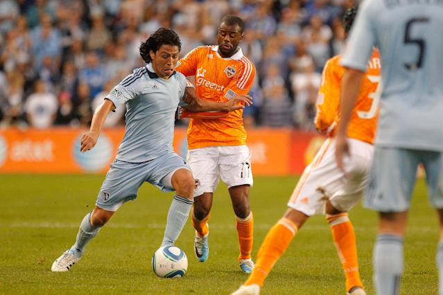 KANSAS CITY, KS - NOVEMBER 06: Roger Espinoza #15 of the Sporting Kansas City attemps to fight past the defense of Luiz Camargo of the Houston Dynamo in the first half during the MLS Eastern Conference Championship match at Livestrong Sporting Park on November 06, 2011 in Kansas City, Kansas. (Photo by Kyle Rivas/Getty Images)