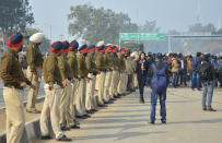 Indian policemen and media person wait for the return of Indian pilot at India Pakistan border at Wagah, 28 kilometers (17.5 miles) from Amritsar, India, Friday, March 1, 2019. Pakistan is preparing to hand over a captured Indian pilot as shelling continued for a third night across the disputed Kashmir border even as the two nuclear-armed neighbors seek to defuse the most serious confrontation in two decades. (AP Photo/Prabhjot Gill)