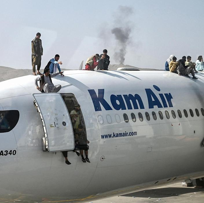Image: Afghan people climb atop a plane as they wait at the airport in Kabul, Afghanistan. (Wakil Kohsar / AFP via Getty Images)