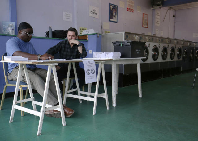 Election volunteers staff a polling station located in a launderette in Headington, England, Thursday May 23, 2019, as polls opened in elections for the European Parliament. (Jonathan Brady/PA via AP)