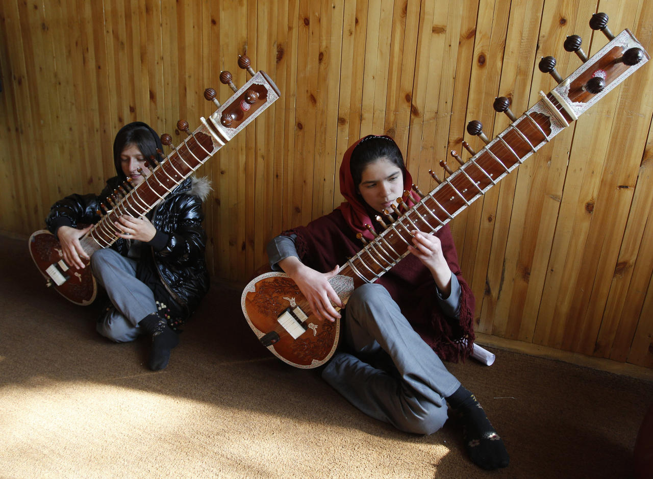 """ATTENTION EDITORS - THIS IMAGE IS 2 of 22 TO ACCOMPANY A PICTURE PACKAGE ON AFGHANISTAN'S ONLY MUSIC ACADEMY, BASED IN KABUL. SEARCH KEYWORD """"MUSIC ACADEMY"""" TO SEE ALL IMAGES PXP700-721.   Afghan women play Sitars at the Kabul Music Academy January 7, 2012. In Afghanistan's sole music academy, students learn how to play traditional and western instruments as part of a government initiative to relieve the pains of decades of war through music. Despite a rich musical legacy, Afghanistan's melodic development has been severely disrupted by years of war and outright banned during the austere rule of the Taliban. At the Afghanistan National Institute of Music, orphans learn how to sing and play instruments alongside talented promising musicians who are selected on merit.  Picture taken January 7, 2012. To match Feature AFGHANISTAN-MUSIC/  REUTERS/Omar Sobhani (AFGHANISTAN - Tags: SOCIETY CONFLICT)"""