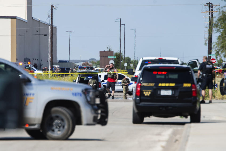 Odessa and Midland police and sheriff's deputies surround an area in Odessa, Texas, after reports of shootings on Saturday.
