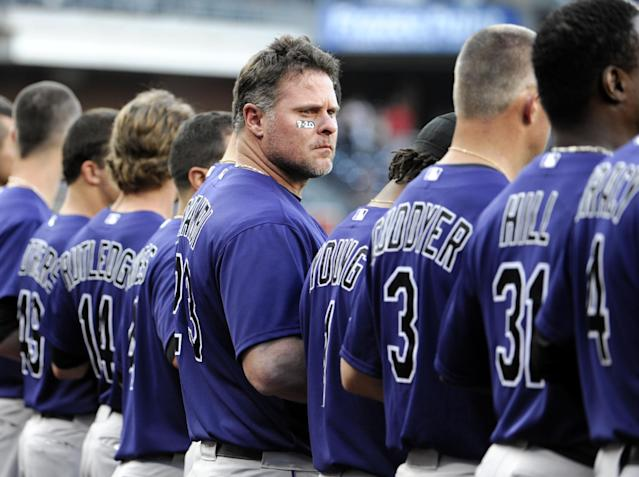 Colorado Rockies' Jason Giambi, center, looks out to the field as players observe a moment of silence for the victims of the Colorado theater shooting before the start of a baseball game against the San Diego Padres Friday, July 20, 2012, in San Diego. The gunman, identified by police as 24-year-old James Holmes, used a military-style semi-automatic rifle, a shotgun and a pistol, stopping only to reload. At least 12 people were killed and several dozens wounded in one of the deadliest mass shootings in recent U.S. history. (AP Photo/Denis Poroy)