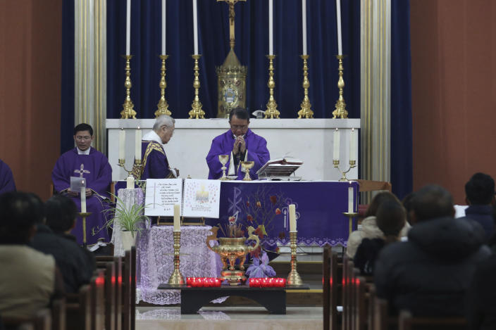 Father Simon Thang Duc Nguyen, center, leads the congregation in prayer during a Mass and vigil for the 39 victims found dead inside the back of a truck in Grays, Essex, at The Holy Name and Our Lady of the Sacred Heart Church, east London's Vietnamese church on Saturday, Nov. 2, 2019. All those killed were Vietnamese nationals, British police said. (Yui Mok/PA via AP)