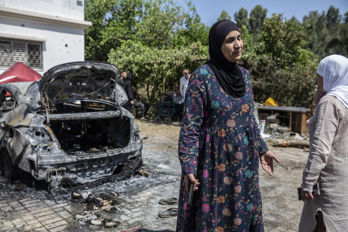 Relatives gather outside the damaged home of Nadine,16, and Khalil Awaad, a father and daughter who were killed by a rocket fired from the Gaza Strip, in their village of Dahmash near the Israeli city of Lod, Wednesday, May 12, 2021. (AP Photos/Heidi Levine)