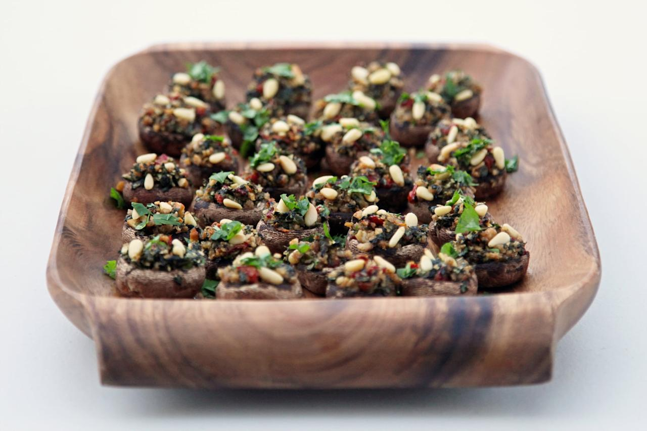 """<p>For a retro nibble with a modern spin, serve <a href=""""https://www.popsugar.com/food/Vegetarian-Stuffed-Mushroom-Recipe-12733327"""" class=""""ga-track"""" data-ga-category=""""Related"""" data-ga-label=""""http://www.yumsugar.com/Vegetarian-Stuffed-Mushroom-Recipe-12733327"""" data-ga-action=""""In-Line Links"""">stuffed mushrooms</a> filled with arugula, walnuts, and sun-dried tomatoes. </p>"""