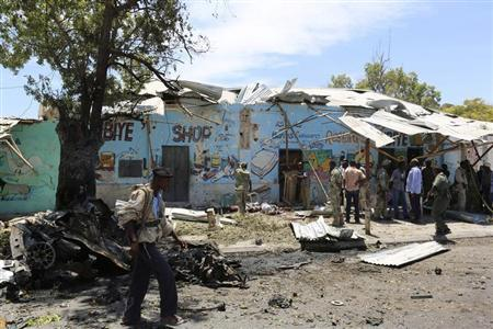A Somali policeman walks at the scene of a suicide car bomb attack next to a tea shop in the suburbs of capital Mogadishu