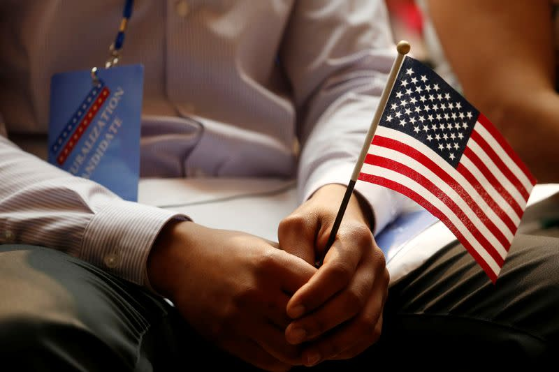 FILE PHOTO: A new citizen holds a U.S. flag at the U.S. Citizenship and Immigration Services (USCIS) naturalization ceremony at the New York Public Library in Manhattan