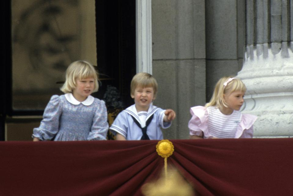 LONDON, ENGLAND - JUNE 15:  Prince William points from the balcony of Buckingham Place with his cousin Zara Phillips (L) and Lady Davina Windsor (R) following Trooping the Colour on June 15, 1985 in London, England. (Photo by Anwar Hussein/Getty Images)