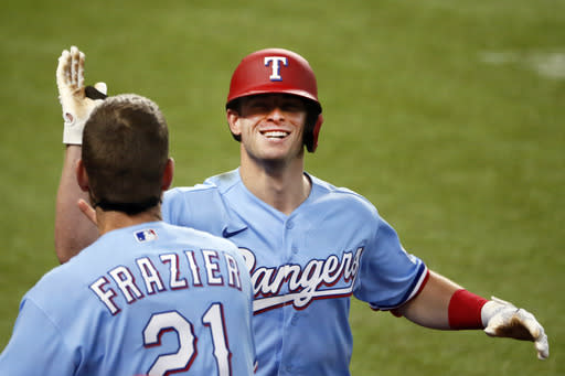Texas Rangers' Nick Solak, right, is greeted at the dugout by Todd Frazier, left, after hitting a solo home run on a fly ball that the popped out of the mitt of Los Angeles Angels right fielder Jo Adell (not pictured) and went over the outfield wall during the fifth inning of a baseball game in Arlington, Texas, Sunday, Aug. 9, 2020. (AP Photo/Ray Carlin)