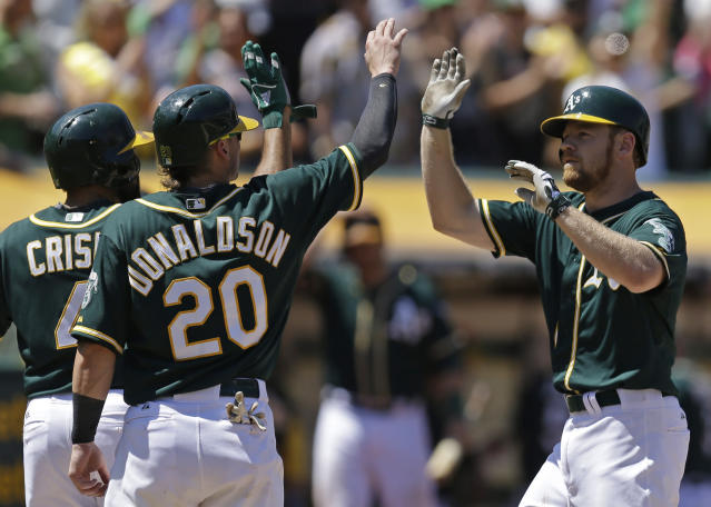 Oakland Athletics' Brandon Moss, right, is congratulated by teammate Josh Donaldson (20) after hitting a grand slam off Houston Astros' Anthony Bass in the sixth inning of a baseball game on Thursday, July 24, 2014, in Oakland, Calif. (AP Photo)